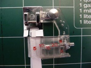 Insert double fold bias tape into bias tape presser foot and adjust backstop (Sewn By Tanya Sewing Tip)