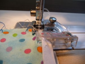Bias tape being attached to a fabric edge using bias tape foot (Sewn By Tanya Sewing Tip)