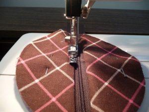 Using a narrow zipper foot to sew on a zipper