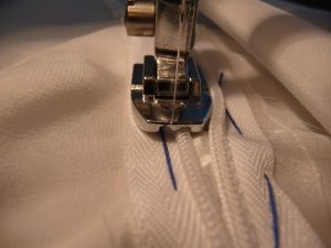 Close up of invisible zipper foot being used to sew an invisible zipper