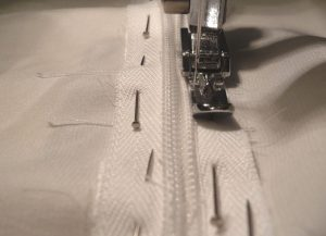 Close up of narrow zipper foot being used to sew an invisible zipper