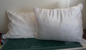2 white silk pillowcases with pillows inside on a green table