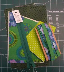 Zipper, cut fabric and bias tape on a green cutting mat