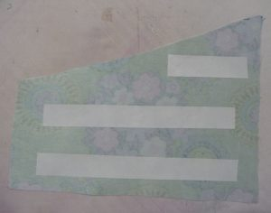 Wrong side of fabric showing paper-backed iron-on adhesive