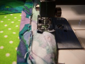 Closeup showing bias tape being sewn on with a universal presser foot