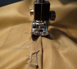 Closeup of sewing a flat felled seam in khaki silnylon