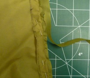 Closeup of trimming seam allowance in khaki silnylon with a green background