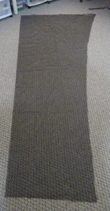Black mosquito mesh peices on a grey carpet