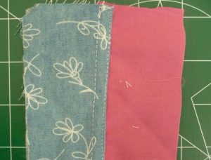 Bleu floral fabric sewn to pink fabric using top-stitiched french seam