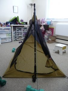 Front view of triangular prism-shapped shelter made front khaki silnylon & black mosquito mesh