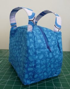 Oblique view of blue Chubby Lunch Tote with blue/white/black handles curving upward