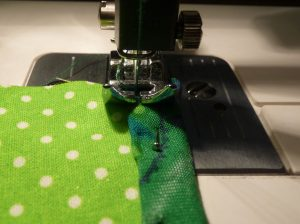 Close up of sewing solid green fabric to pale green fabric with white dots