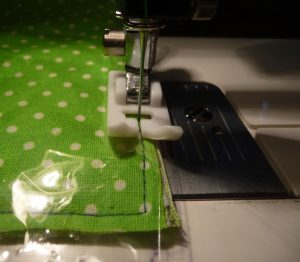 Closeup of sewing clear vinyl onto light green pfabric with white dots