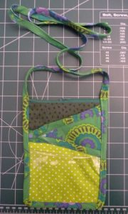 Finished green DIY Neck wallet on a green background