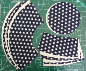 3 piles: Blue with white dots hat pieces on cream colored hat peices