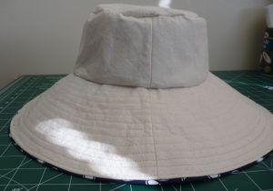 Side view finished sun hat cream side with blue piping