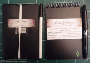 Black agenda with elastic band on the cover, pen, black notebook with white business cards on the cover and another pen