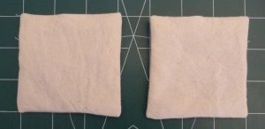 2 cream fabric squares (hand warmer interiors) on a green background