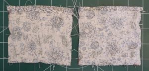 2 squares of blue floral fabric wrong sides up for hand warmer exteriors