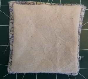 Cream fabric square on top of a slightly largter blue floral square