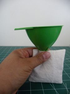 left hand holding a green funnel in a cream hand warmer interior
