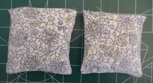 2 blue floral, square hand warmers on a green background