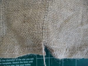 Closeup of pulling a thread from burlap