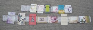 Multicolored greeting cards on the long and short card holders, grey carpet in background
