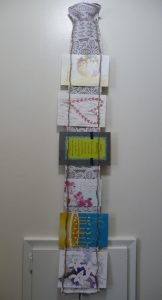 Short card holder with multicolored cards hanging on a cream-colored wall