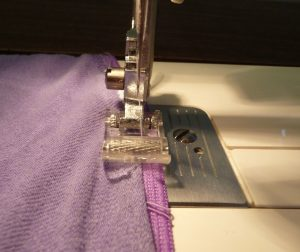 Close up of using a roller foot to sew purple cotton jersey onto purple elastic