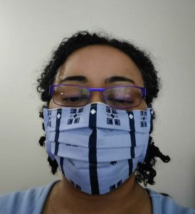 Woman with glasses wearing Pleated Rectangular Mask  (pale blue with navy accents)