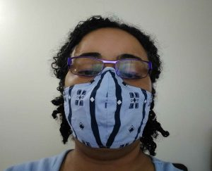 Woman with glasses wearing Olson-Style Mask (pale blue with navy accents)
