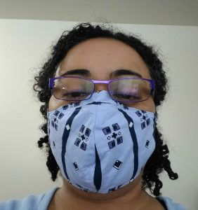 Woman with glasses wearing Modified Olson-style Mask (pale blue with navy accents)