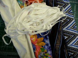 Close up of white elastic, white cotton, floral, black striped and multicolored zigzag fabrics
