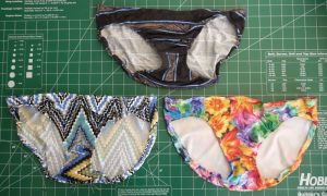 Front view of balck striped panties, multicolor zigzag panties and floral panties on a green background