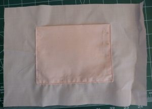 Peach bag lining with a matching pocket on a green background