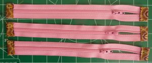 3 pink zippers with orange ends on a green background