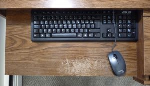 Black keyboard and mouse on a brown keyboard shelf with some damage