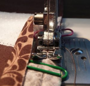 Close up sewing unfolfed brown bias tape along the edge of brown floral desk mat