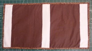 Rear view of desk mat showing white grip fabric on the brown back panel