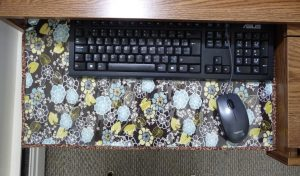 Black keyboard and mouse, and brown floral desk mat on a medium brown desk