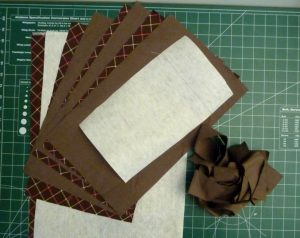 Brown fabric, white stabilizer and brown binding strips on a green background