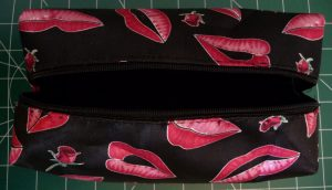 How To Replace a Zipper - Good Candidate this open black pouch with a pink lip pattern showing black interior and damaged zipper tape