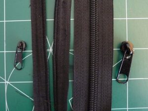 Damaged #3 zipper (left) & new replacement #5 zipper (right) on a green background