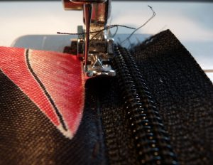 Top stitiching along black zipper tape and black and pink fabric