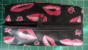 Black pouch with pink lips pattern with new black zipper (zipper halfway open)