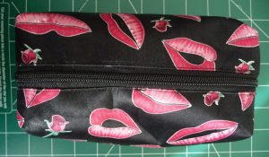 Black pouch with pink lips pattern with new black zipper (zipper closed))