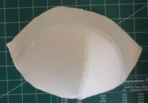 Cream-colored Maya Bra foam cup on a green mat