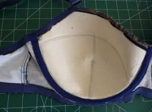 Inside of Maya Bra cup showing cream colored foam, navy blue underwire channeling, and lined wing and bridge