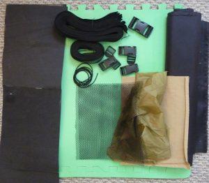 Black webbing, hardware, mesh & EVA foam, and khaki silnylon all on a background of green eva foam